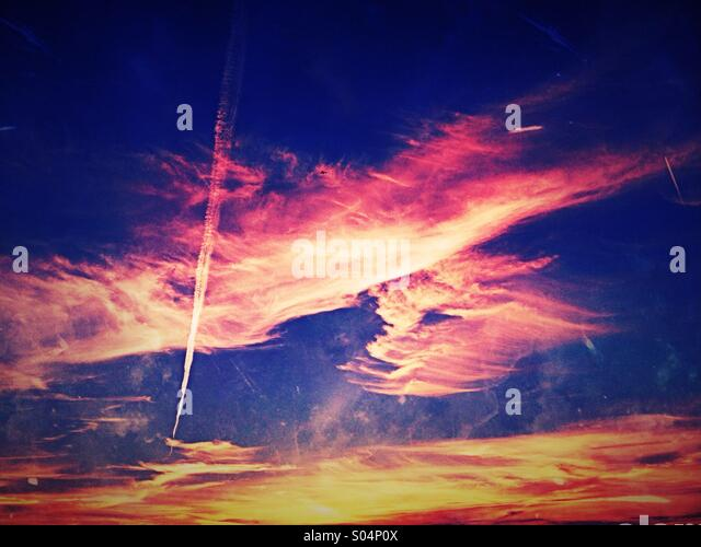 Vapour trail and clouds at sunset - Stock Image