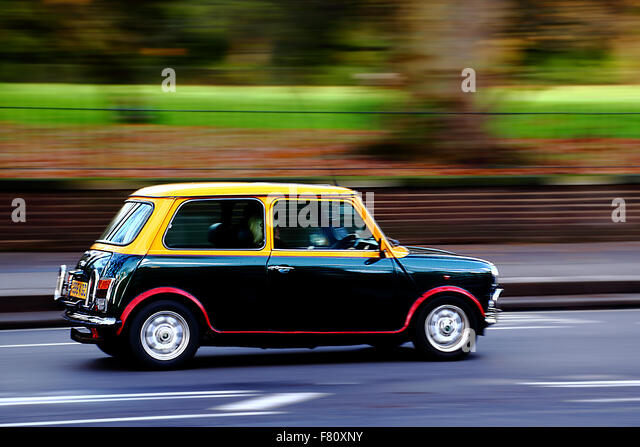 Original Mini travelling through Kensington, London, UK - Stock Image