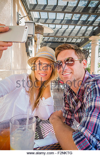 Caucasian couple taking cell phone selfie at lunch - Stock Image