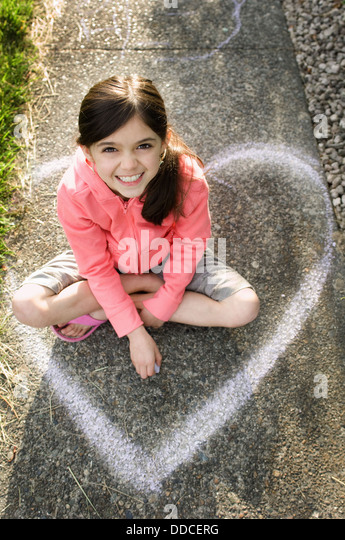 Young girl, elementary age, playing outside and drawing with chalk. Kids at play. - Stock Image