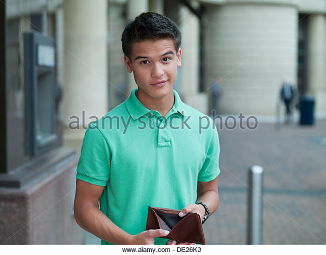 Unhappy man holding empty wallet near ATM machine - Stock Image