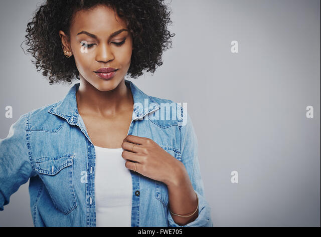Thoughtful attractive young African American woman wearing a casual denim jacket standing with downcast eyes looking - Stock Image