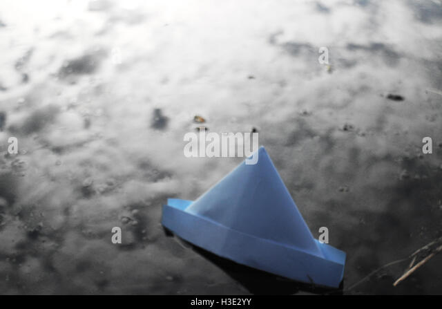 A photo of a paper boat floating in a lake, with the refection of the sky in the water. Reminiscent of childhood - Stock-Bilder
