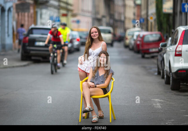 Teenage girls in the street of the old town. One girl sits on the chair on the road, the second girl was behind - Stock Image