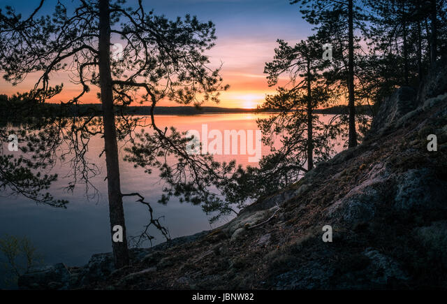 Scenic landscape over lake with sunset at spring evening in Finland - Stock Image