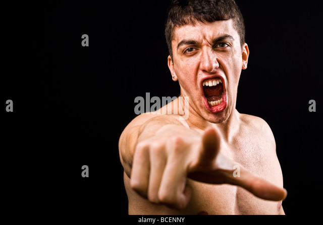 Loud scream of angry furious violent man pointing towards camera - Stock Image