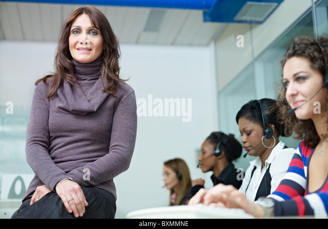 confident businesswoman with multiethnic group of female customer service representatives talking on the phone. - Stock Image