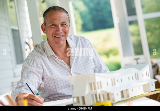 A farmhouse kitchen. A model of a house on the table. Designing a house. A man using a pencil drawing on a plan. - Stock Image