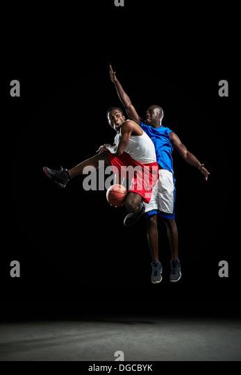 Male basketball players jumping and shooting ball - Stock Image