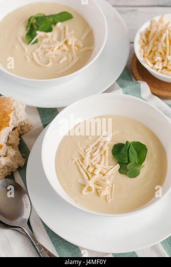 Bowls of cheese soup on table - Stock-Bilder