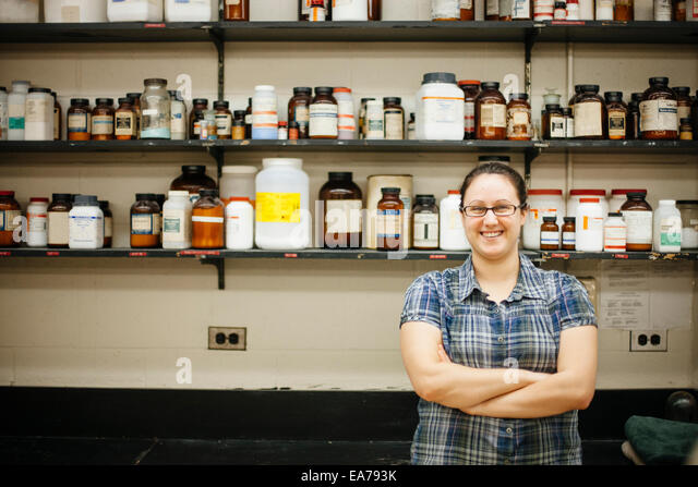 Portrait of smiling mid-adult woman against wall mounted shelves with laboratory bottles - Stock Image