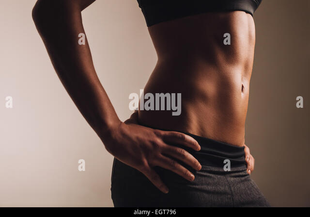 Close-up shot of young woman waist with muscular abdominal muscles. Abs of fit female athlete. - Stock Image