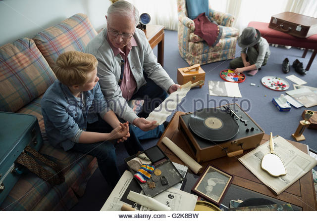 Grandfather and grandson looking through old memorabilia - Stock-Bilder