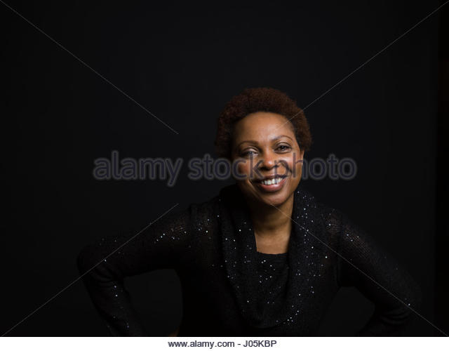 Portrait confident, smiling African American woman with hands on hips against black background - Stock Image