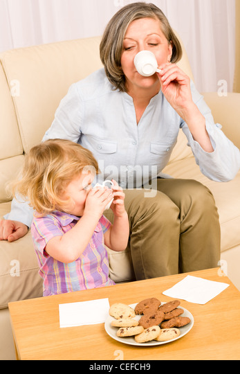 Little granddaughter with grandmother eat cookies drink tea cup together - Stock-Bilder