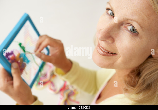 Mid age woman doing cross stitch - Stock Image
