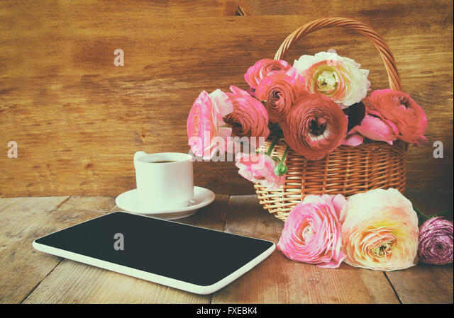 cup of coffee next to tablet and flowers on wooden table. vintage filtered and toned - Stock Image