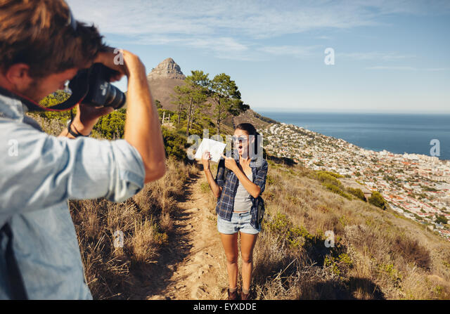 Excited young woman showing map and posing to his boyfriend taking her pictures with digital camera. Young couple - Stock Image