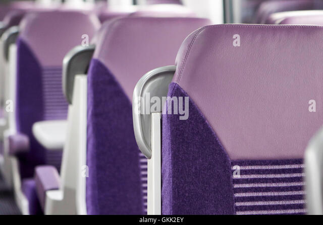 row of empty train carriage seats in ireland - Stock Image