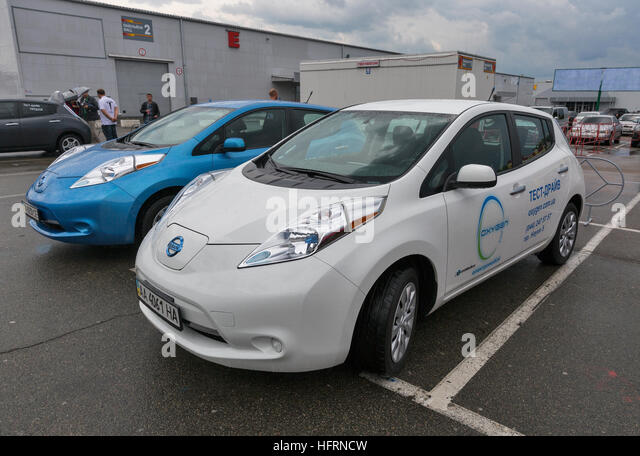 Visitors visit Oxygen Nissan Leaf electric hybrid cars parked outdoor on display at rade Show of Electric Vehicles. - Stock Image