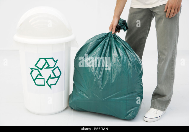 Man holding large garbage bag next to recycling bin, cropped view - Stock Image