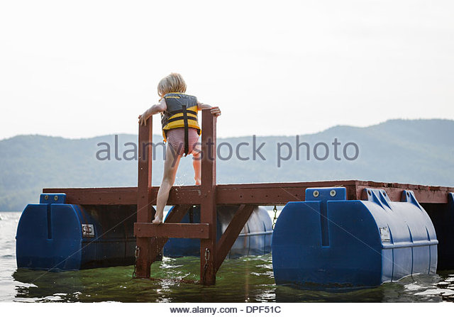 Female toddler climbing out of lake, Silver Bay, New York, USA - Stock Image