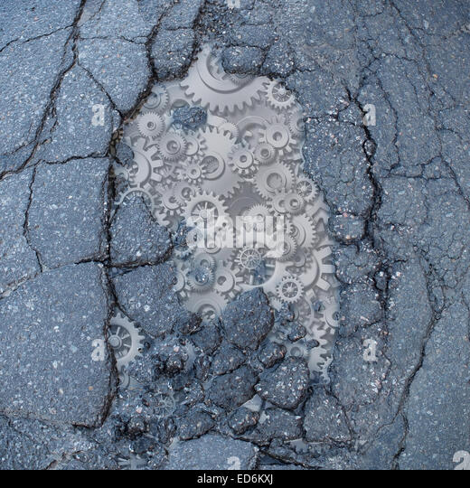 Public works and transportation concept as a broken asphalt road with gears and machine cog wheels as a metaphor - Stock Image