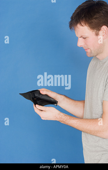 Man holding empty wallet - Stock Image