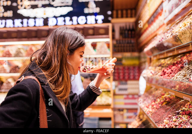 Young woman smelling food in market, Istanbul, Turkey - Stock Image