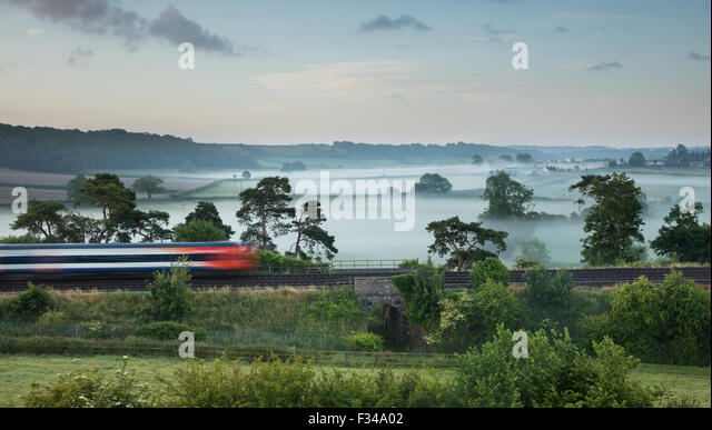 the London Waterloo to Exeter train passing Milborne Wick on a misty summer's morning, Somerset, England, UK - Stock Image