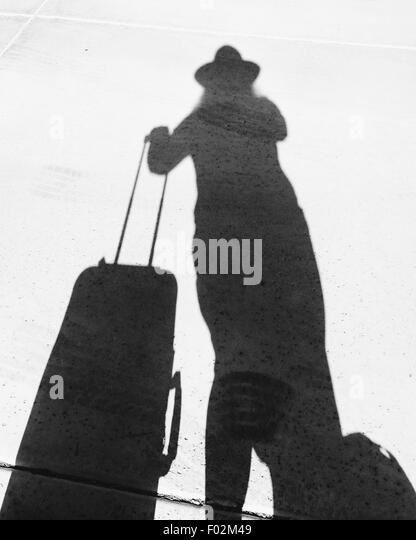 Shadow of a woman with a suitcase - Stock Image