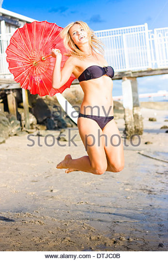 Woman with red umbrella jumping at beach - Stock Image