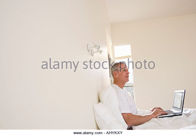 Mature man sitting upright in bed, using laptop, smiling, profile tilt - Stock Image