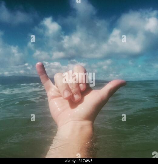 A right hand giving the Shaka sign.  The shaka sign, sometimes known as 'hang loose', is a gesture of friendly - Stock Image