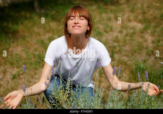 Mid adult woman crouching smelling lavender, eyes closed, arms open - Stock Image