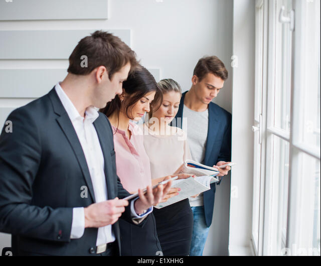 Young business people working by window in office - Stock Image