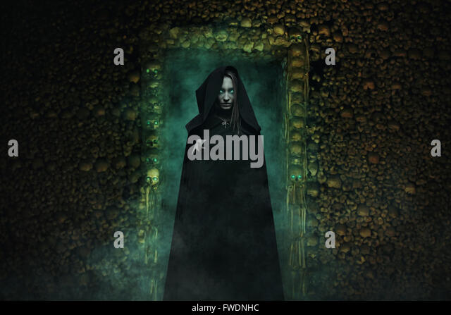 Dangerous vampire in catacombs full of skulls and bones . Horror and fantasy - Stock-Bilder