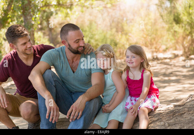 Male couple sitting on riverbank with two daughters - Stock-Bilder