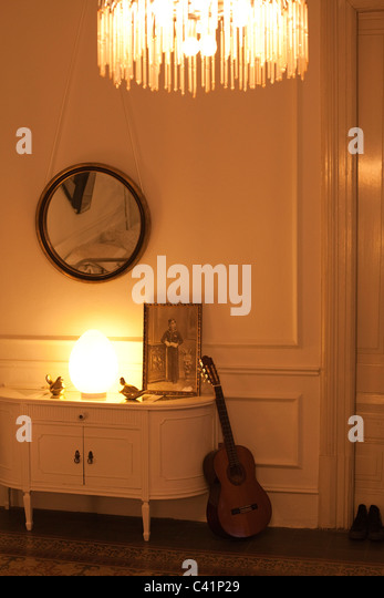 Home interior lit by lamp and chandelier - Stock Image