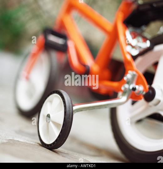 Child's bike with training wheels, close up - Stock-Bilder