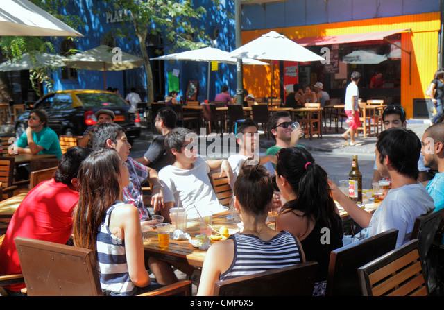 Santiago Chile Bellavista Pio Nono restaurant sidewalk cafe alfresco dining drinking beer Hispanic man woman young - Stock Image