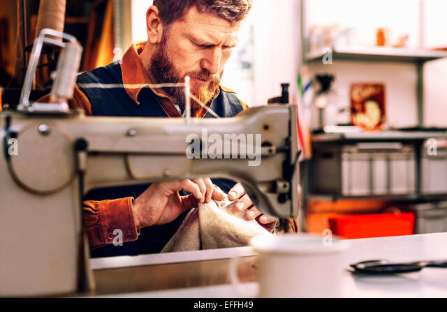 Worker holding fabric at sewing table in workshop - Stock Image