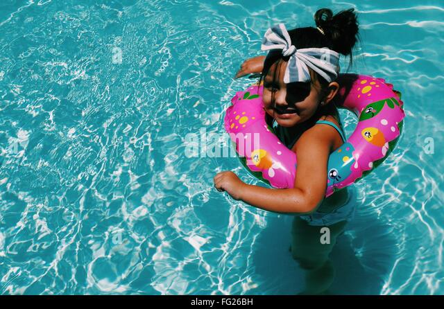 High Angle View Of Happy Girl Swimming In Pool With Life Belt - Stock Image
