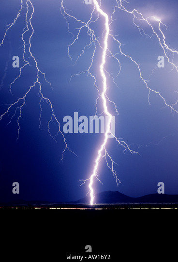 Cropped shot of a huge singular lightning bolt striking against a dark blue sky outside of Tucson, Arizona, USA - Stock Image