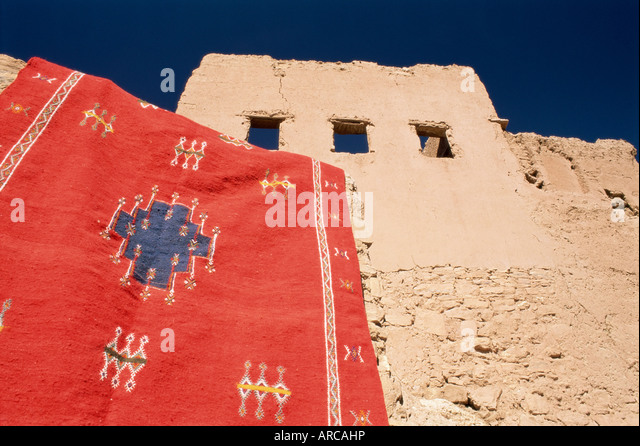 Red carpet drying in the sun, with mud house behind, Kasbah Ait Benhaddou, near Ouarzazate, Morocco, North Africa, - Stock-Bilder
