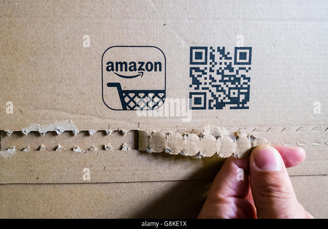 Customer opening a cardboard packet received  from Amazon.com online shop - Stock Image