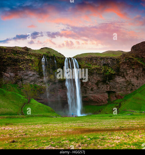 Morning view of Seljalandfoss Waterfall on Seljalandsa river in summer. Colorful sunrise in Iceland, Europe. - Stock Image