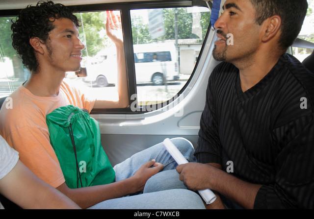 Managua Nicaragua bus to Granada microbus public transportation Hispanic man talking conversation young adult passenger - Stock Image