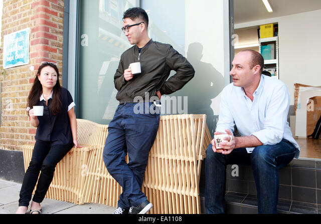Three architect colleagues taking coffee break outside office - Stock Image