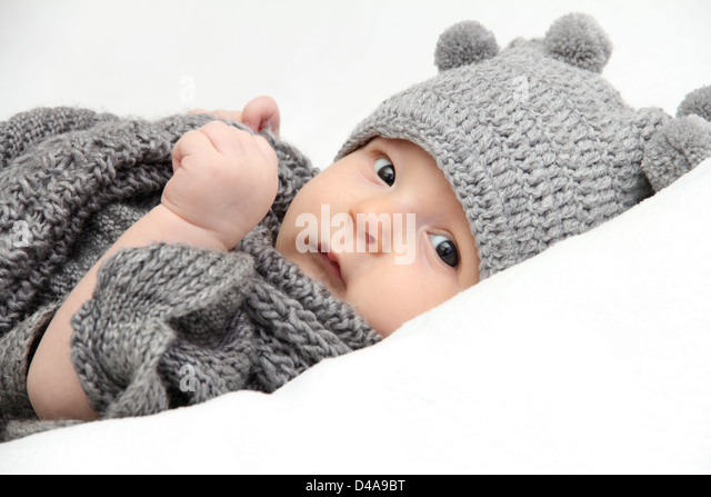 Beautiful baby in gray knitted hat - Stock Image
